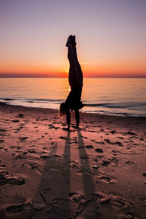 Femme faisant un équilibre sur une plage